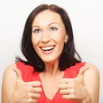 Mujer joven hermosa sonriente que muestra los pulgares arriba gesto