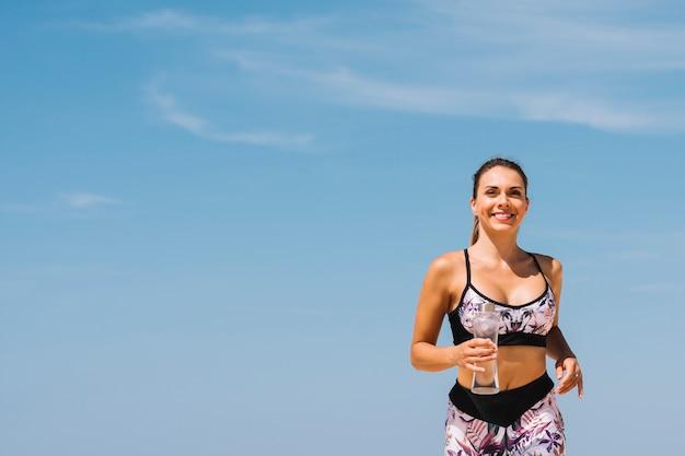 Mujer joven hermosa sonriente que sostiene la botella de agua en la mano que corre contra el cielo azul