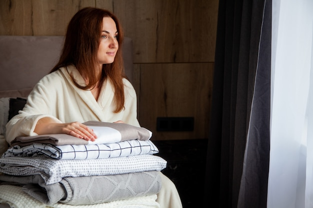 Mujer joven con hermosa sonrisa en cálida túnica beige se apoya en la pila de sábanas dobladas en diferente textura. ropa de cama de algodón natural y orgánico. copie el espacio. fabricar. industria hotelera.