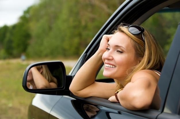 Mujer joven hermosa sonrisa en el coche nuevo - al aire libre