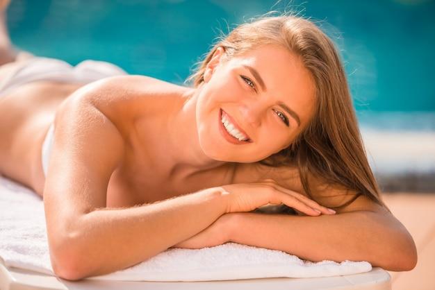 Mujer joven hermosa con sonrisa y que miente en el sillón.