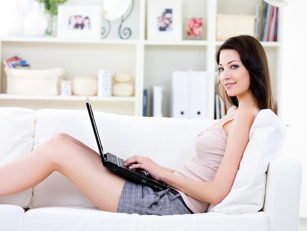Mujer joven con hermosa sonrisa relajándose en el sofá y usando laptop - en el interior