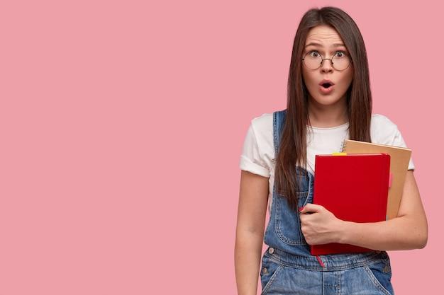 Mujer joven hermosa sorprendida con apariencia asiática, maquillaje, sostiene cuadernos, viste ropa casual