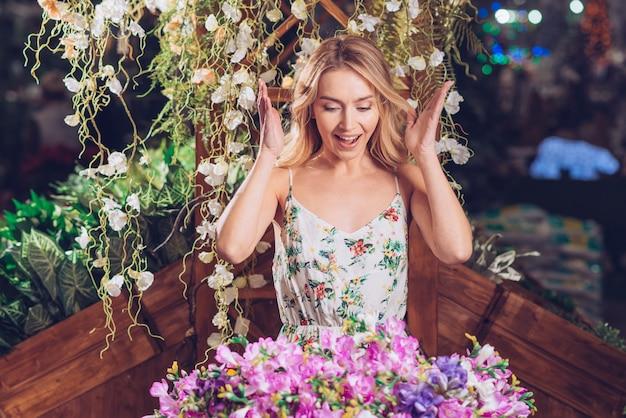 Mujer joven hermosa sorprendida que mira el ramo colorido de la flor en el jardín