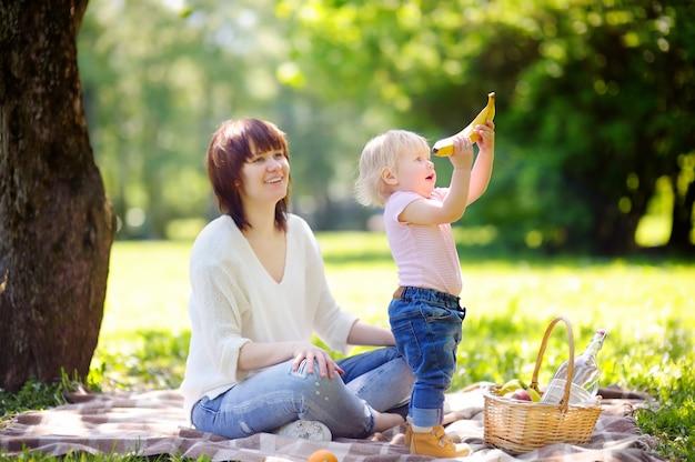 Mujer joven hermosa y su pequeño hijo adorable que tienen una comida campestre en parque soleado