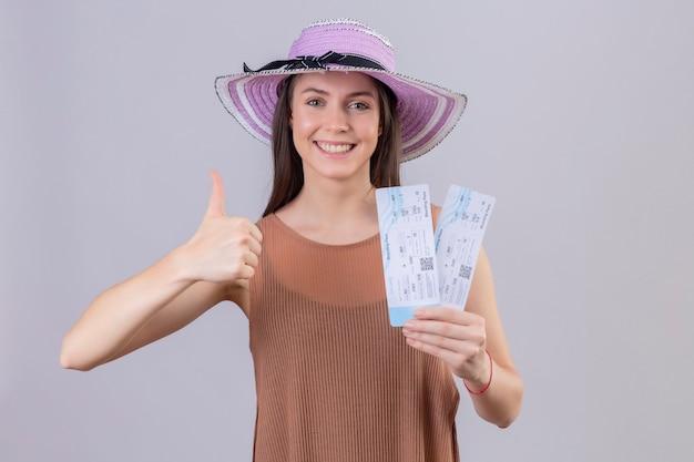 Mujer joven hermosa viajera con sombrero de verano sosteniendo billetes de avión sonriendo con cara feliz mostrando los pulgares para arriba sobre fondo blanco