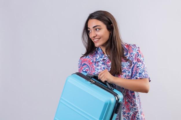 Mujer joven hermosa viajera sosteniendo la maleta mirando seguro positivo y feliz sonriendo alegremente listo para viajar de pie sobre fondo blanco.
