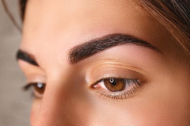 Mujer joven con hermosas cejas después de la corrección, primer plano