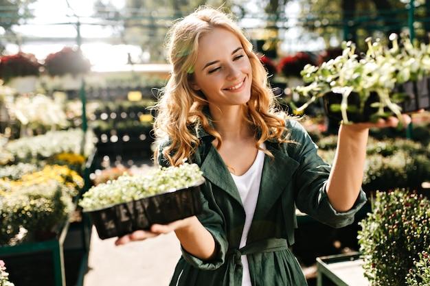 Mujer joven con hermoso cabello rubio y sonrisa suave, vestida con túnica verde con cinturón está trabajando en invernadero
