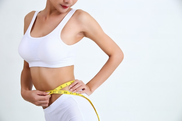 Mujer joven con hermoso cuerpo y cinta métrica