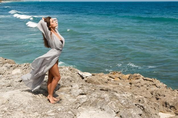 Mujer joven en hermoso vestido en la playa rocosa