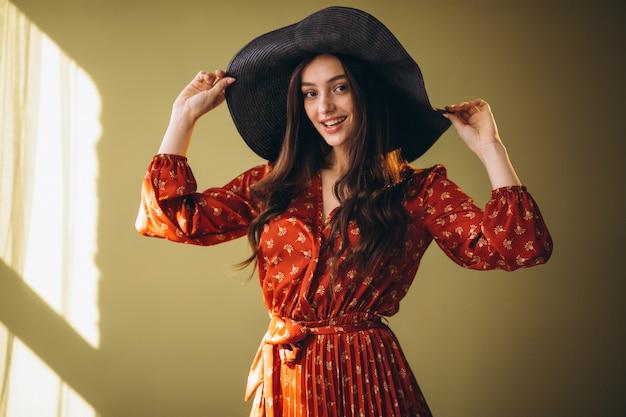Mujer joven en un hermoso vestido y sombrero