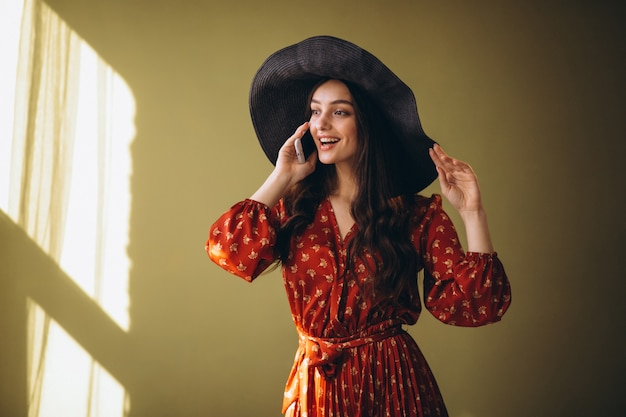 Mujer joven en un hermoso vestido con teléfono y compras en línea