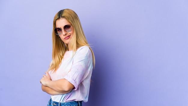 Mujer joven hipie con gafas aisladas en púrpura sospechoso, incierto, examinándote.