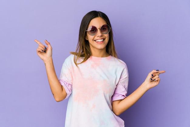 Mujer joven hippie apuntando a diferentes espacios de copia, eligiendo uno de ellos, mostrando con el dedo.