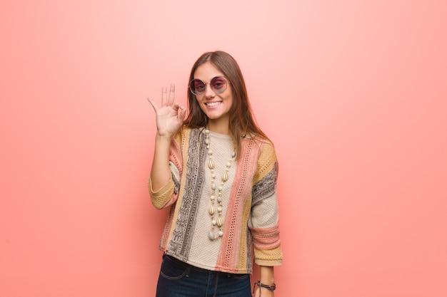Mujer joven del hippie en gesto que hace alegre alegre y confidente rosado