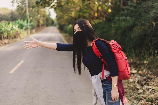 Mujer joven hippie con mascarilla haciendo autostop.