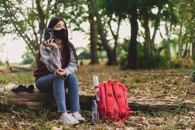 Mujer joven hippie con mascarilla tomando fotografías.