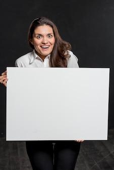 Mujer joven con hoja de papel en blanco