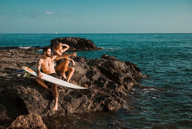 Mujer joven y hombre apuntando al lado con tablas de surf en roca cerca del mar