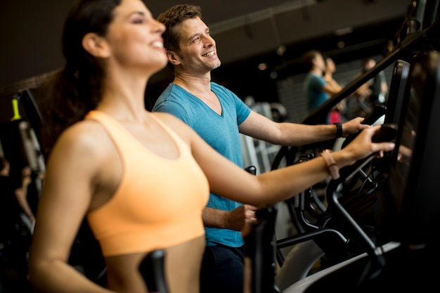 Mujer joven y hombre en el entrenador paso a paso elíptico que ejercita en gimnasio