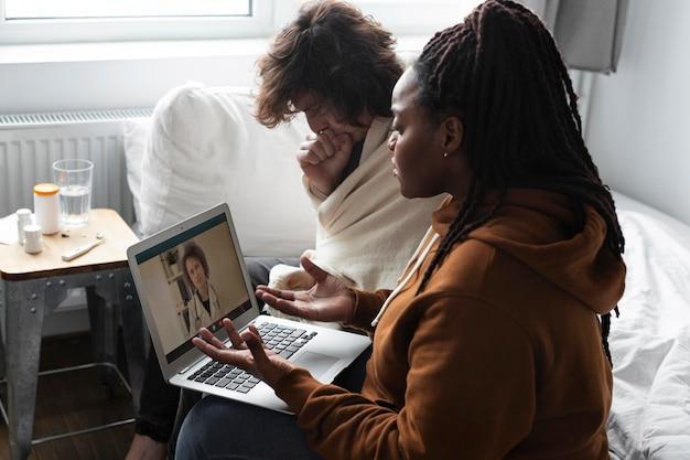 Mujer joven y hombre hablando con un médico en línea