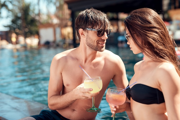 Mujer joven con el hombre joven en piscina junto.