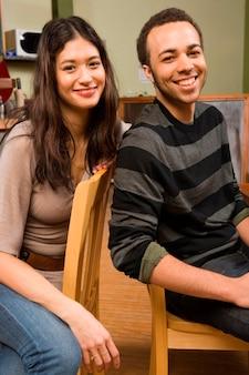 Mujer joven y hombre en sillas de comedor