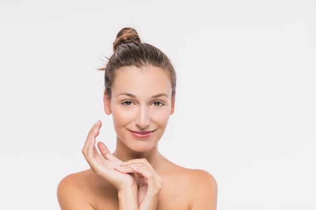 Mujer joven con hombros desnudos sobre fondo blanco