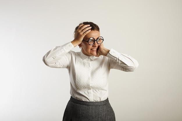Mujer joven horrorizada tiene la cabeza entre las manos y mira a la distancia aislado en blanco