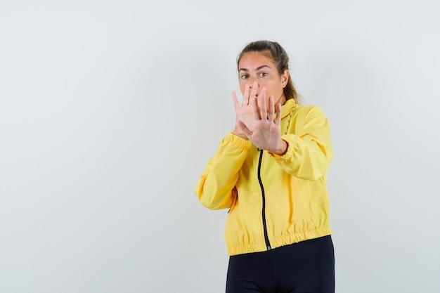 Mujer joven en impermeable amarillo levantando las manos defendiéndose y mirando preocupado