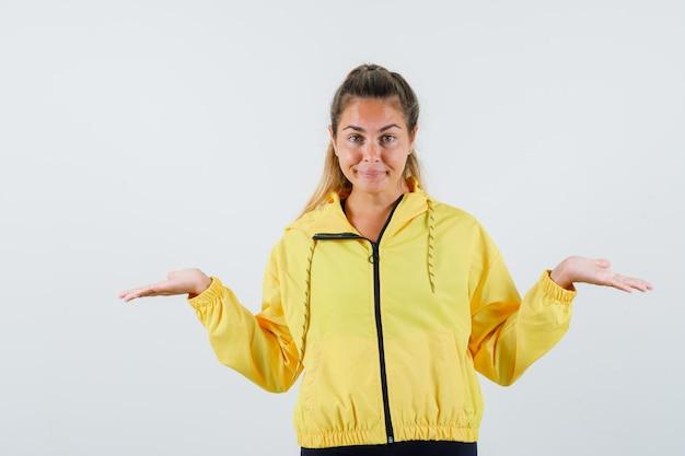 Mujer joven en impermeable amarillo mostrando gesto de impotencia
