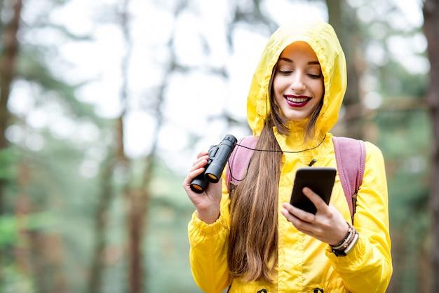 Mujer joven en impermeable amarillo con teléfono inteligente para orientación durante la caminata en el bosque de pinos verdes