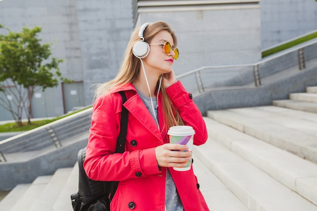 Mujer joven inconformista en abrigo rosa, jeans en la calle con mochila y café escuchando música en auriculares, con gafas de sol