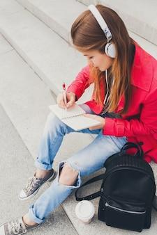 Mujer joven inconformista en abrigo rosa, jeans sentado en la calle con mochila y café escuchando música en auriculares, estudiante haciendo notas