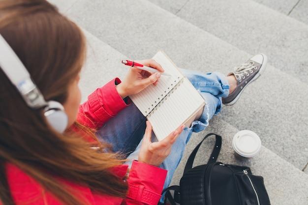 Mujer joven inconformista en abrigo rosa, jeans sentado en la calle con mochila y café escuchando música en auriculares