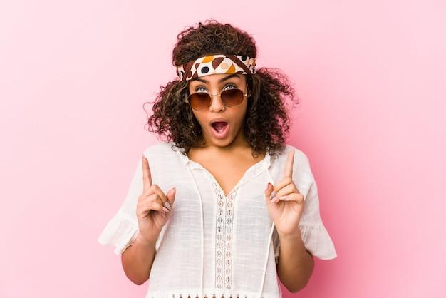 Mujer joven inconformista afroamericana aislada en pared rosa apuntando al revés con la boca abierta.