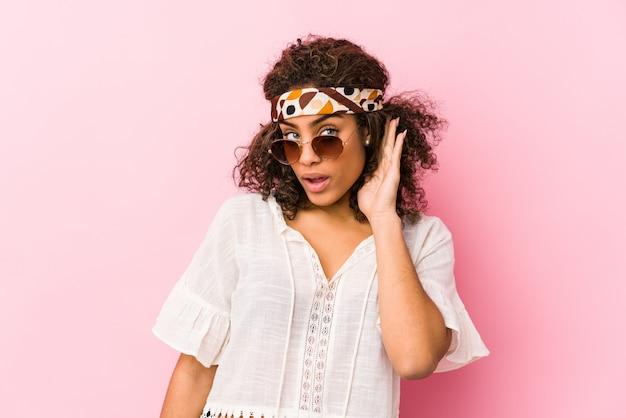 Mujer joven inconformista afroamericana aislada en la pared rosa tratando de escuchar un chisme.