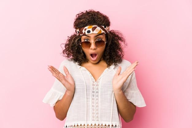 Mujer joven inconformista afroamericana aislada sobre fondo rosa sorprendido y conmocionado.