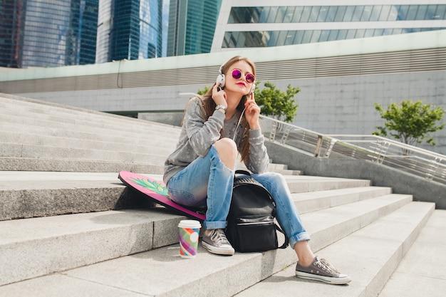 Mujer joven inconformista en la calle con tabla de equilibrio vistiendo suéter y jeans