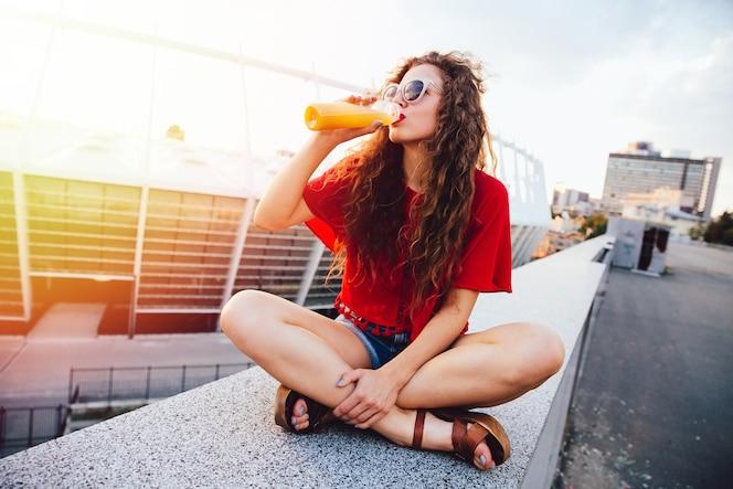 Mujer joven inconformista con el pelo rizado en gafas de sol bebiendo jugo de naranja fresco de la botella