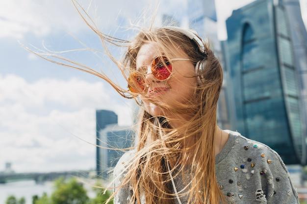 Mujer joven inconformista divirtiéndose en la calle escuchando música en auriculares, con gafas de sol rosa