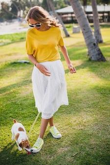 Mujer joven inconformista con estilo sosteniendo caminar y jugar con el perro en la playa