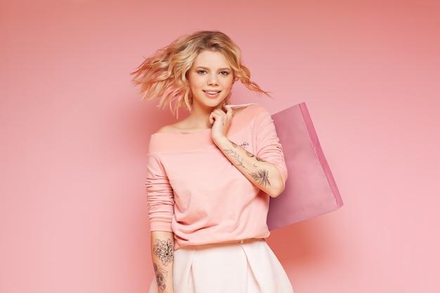 Mujer joven del inconformista del estudiante con los pelos que vuelan coloreados y el tatuaje que sostiene el bolso de la tienda.