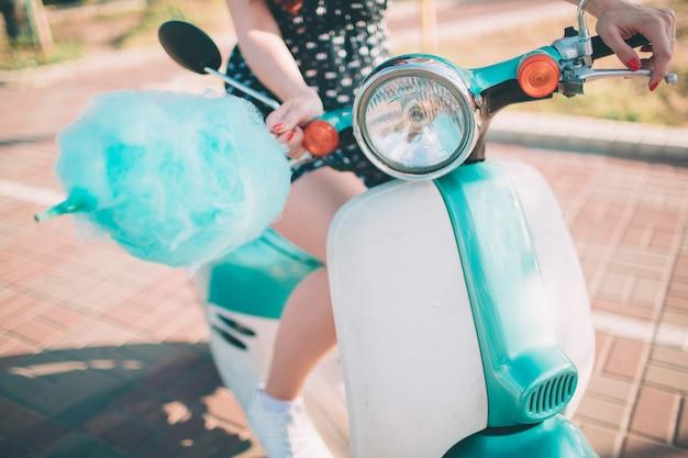Mujer joven inconformista feliz comiendo algodón de azúcar endulzado. modelo femenino montando un scooter azul una calle de la ciudad.