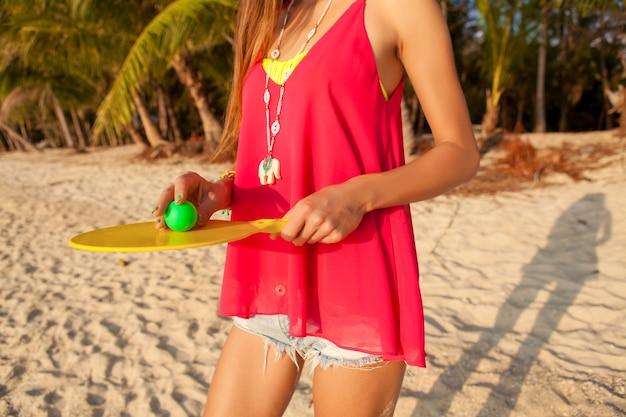 Mujer joven inconformista jugando ping-pong en playa tropical, vacaciones de verano.