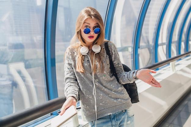 Mujer joven inconformista en outfi casual en suéter y gafas de sol, estudiante haciendo notas, expresión de la cara perpleja, problema