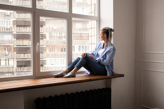 Mujer joven inconformista con rastas sentado en el alféizar de la ventana
