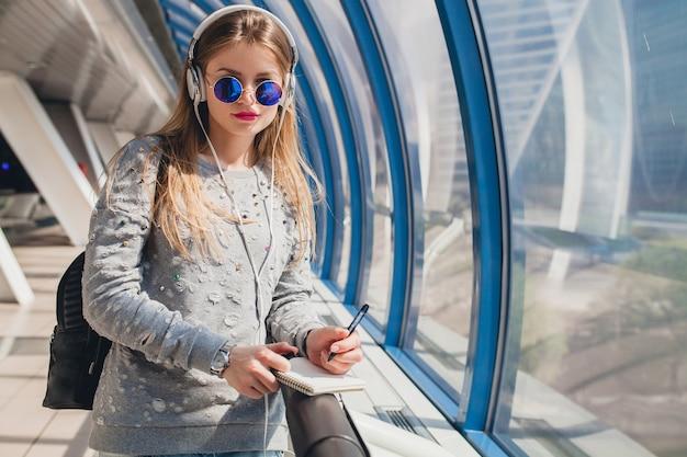 Mujer joven inconformista en ropa casual divirtiéndose escuchando música en auriculares