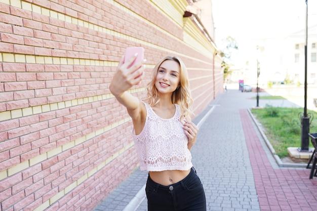 Mujer joven inconformista rubia, haciendo selfie, posando en el campo en el día de verano
